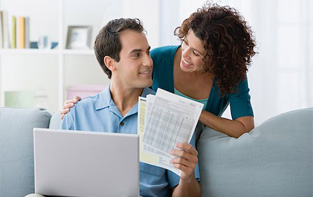 Young woman leaning over her husband while he reviews budget documents and uses the online Debt Management tool.