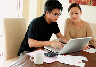 Young couple at the kitchen table using the online savings tool on their laptop.