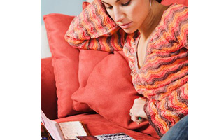 Young woman with her credit cards and cheque book on the couch, calculating her savings.