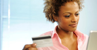 Young woman with her credit card going online to review her spending habits.