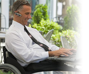 Man in a wheelchair outside using his laptop.