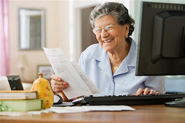 Senior women banking at home with her desktop computer.