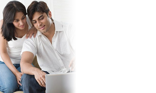 Young couple sitting on a couch reviewing their personal banking information on a laptop