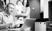 男士使用電腦其妻子與小孩站在身後