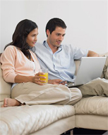 Couple sitting on a couch, using a laptop