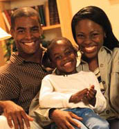 A family smiles in their home.