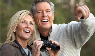 Middle-aged couple outdoors and smiling. The woman is holding a pair of binoculars ready to see what the man is pointing to in the distance.