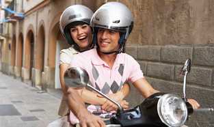 Young couple wearing helmets while riding their moped through a quiet street.