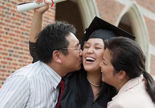 Proud parents hugging their daughter at her graduation.