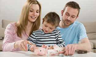 A young couple sitting at the kitchen table with their son breaking open a piggy bank with a small hammer.