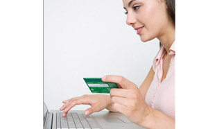 Young woman using her laptop, holding her bank card and ready to log in to use the EasyWeb Tour Tool.