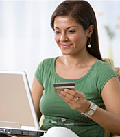 A smiling woman enters her credit card information on the computer